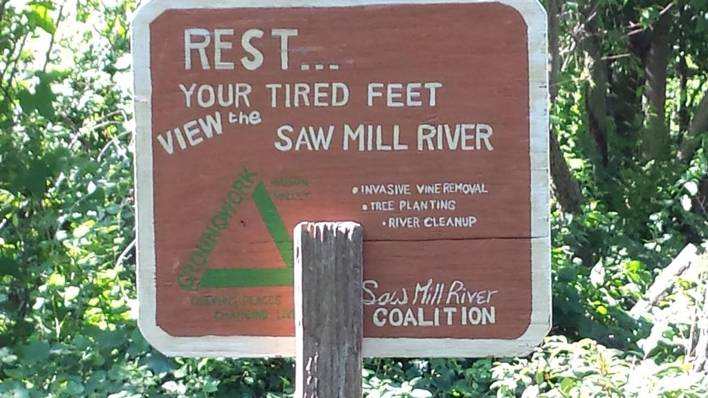 Sign saying to rest your tired feet and view the saw mill river