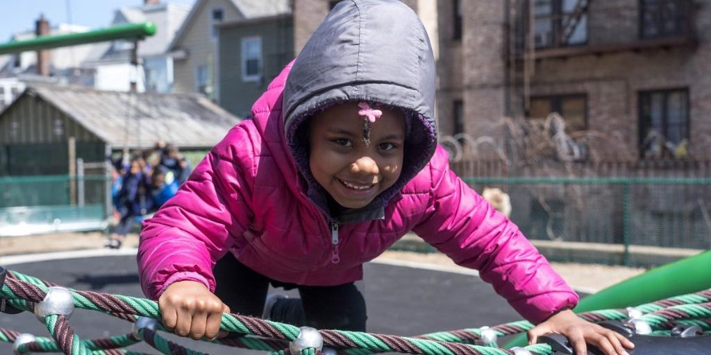 Small child smiling at camera on playground