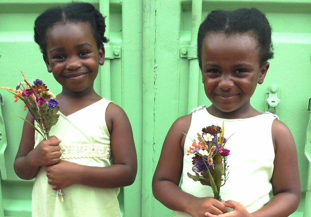 two cute black girls holding flowers and smiling